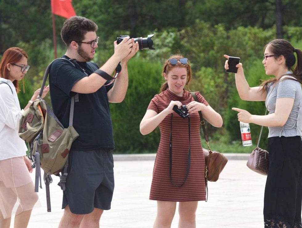 参观成吉思汗陵时,来自美国的Dylan(左2)和Isabella(左3)用镜头记录中国大学生的身影。