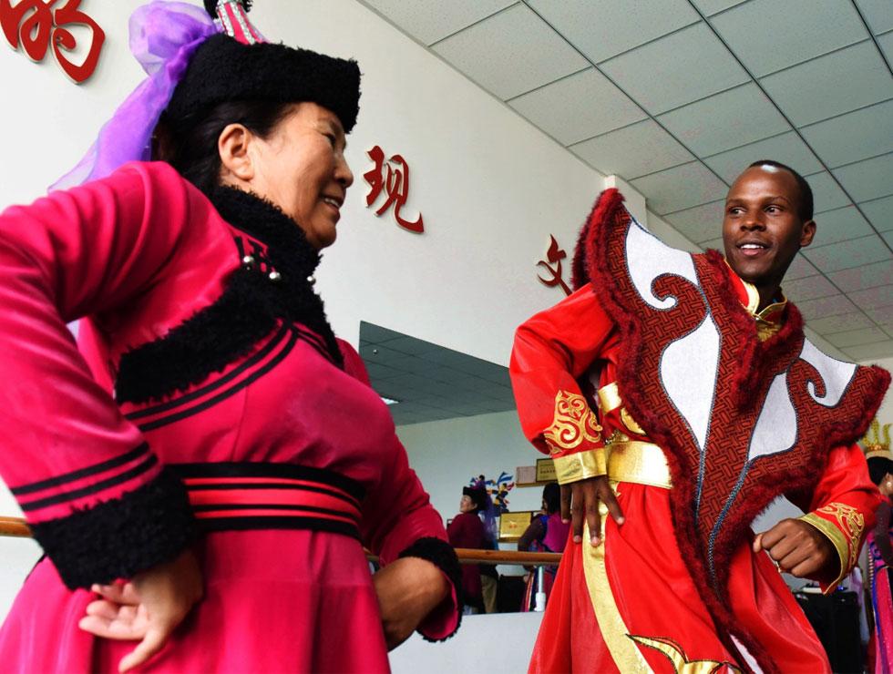 """肯尼亚大学生Nelson向乌审""""文化独贵龙""""演员学习蒙族舞蹈。"""