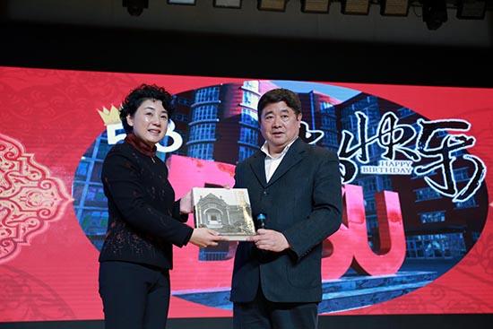 故宫博物院院长单霁翔(右)向北京第二外国语学院党委书记顾晓园(左)赠送礼物