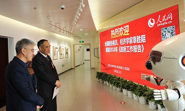 全国政协委员、经济学家辜胜阻(左2)与汪仔交流。    人民网记者 蒋建华 摄