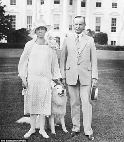 加尔文・库利奇和夫人在白宫草坪上和宠物狗在一起。