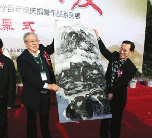 17日上午,曾担任邓小平办公室警卫秘书的张宝忠中将(左)向广安市政府赠送书画作品。