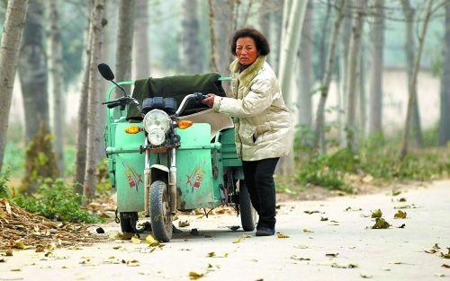 每天要骑着三轮车去为狗狗买粮,电动车没电了只好推着回来。