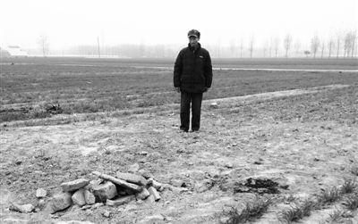 11月22日,张方站在父母的坟前,墓碑已被推倒掩埋。挖墓碑时,他的三儿媳和二妹夫被倒下的墓碑砸死。新京报记者 孟祥超 摄
