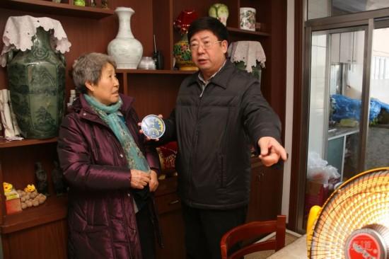 杜吉明同志在居民家中测量供热温度。