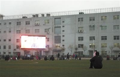 11月2日下午,一些工人坐在富士康园区操场的草皮上,正在看屏幕里播放的《武林外传》。新京报记者 尹聪 摄