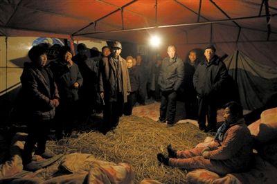 昨日,安徽颍上县迪沟镇,村民在扣留的大巴车旁搭起帐篷。新京报记者 侯少卿 摄