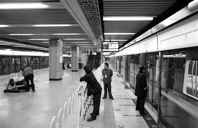 北京/昨日,地铁4号线国家图书馆站,几名工作人员在9号线列车旁。