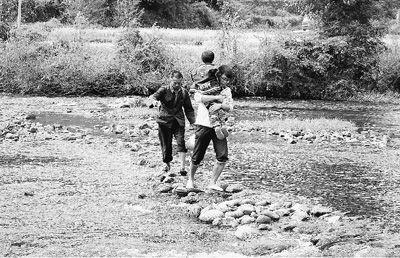 杜鲁宁抱小孩过河。