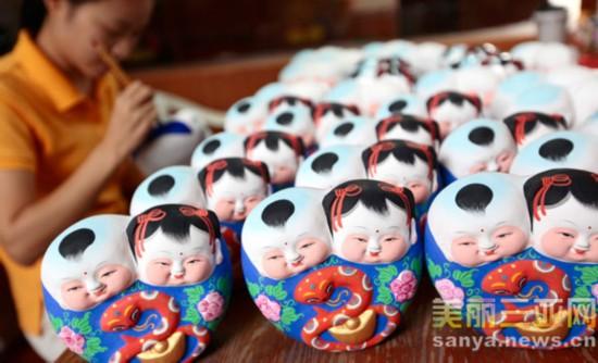 """1月8日,海南省三亚市南山景区喻氏抟泥坊的一名女工在绘制泥塑工艺品""""蛇娃""""。"""