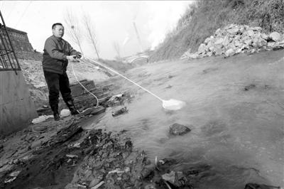 工作人员正在对水进行取样检验。本报记者徐晓帆摄