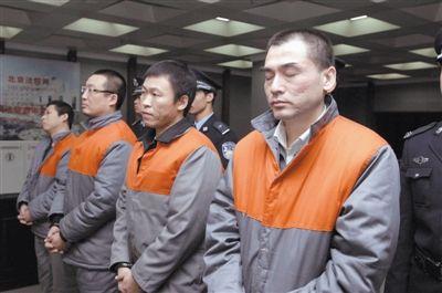 夏克明(右一)等4名被告人在法庭上受审,夏克明闭着眼睛。法院通讯员 摄