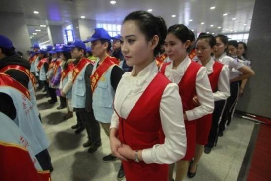 """""""短裙浓妆志愿者""""为铁路局职工,旁边佩戴绶带的为大学生志愿者"""