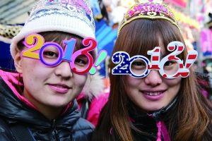 """▲戴着""""2013""""造型眼镜的年轻人。新年到来让人们充满了喜悦和憧憬。 新华社发"""
