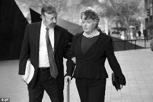 2月14日,身体孱弱的欧康纳(右)手持拐杖在辩护律师的搀扶下出庭