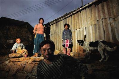 云南省开远市红坡头村,吴笑林一家在自己的棚屋前。他们一家和村里大多数人一样都没有户口,不能外出务工,只能靠种地过活,全家年收入5千元左右。当地每户人家都有好几个孩子,住简陋的棚屋,生活水平非常低。