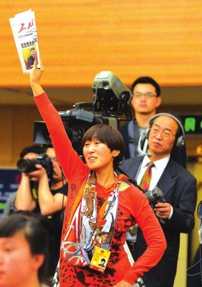 """图为由于提问者太多,一位《工人日报》的女记者情急之下,举起一份工人日报,站在凳子上高声大喊:""""请给工人阶级一个提问的机会!""""引起了现场一片笑声。 (图片来源:兰州晚报)"""