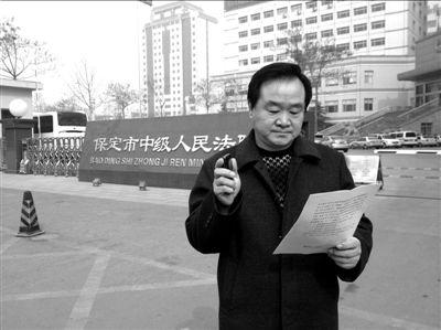 焦占军在法院门口拿着决定书,无语站立。京华时报记者孙思娅摄
