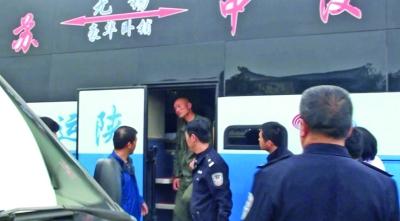 刘钰/歹徒(圈中人)被民警拉着手下了车。刘钰摄