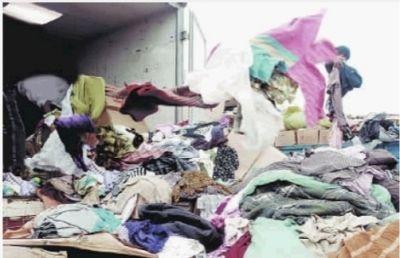 装卸工人正在清理各种洋垃圾的打包服装。 (资料图片)