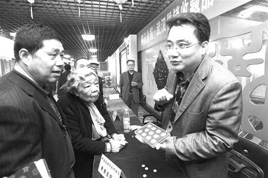 图为:免费鉴定钱币后,专家为藏友讲解钱币收藏知识 (记者曹大鹏摄)