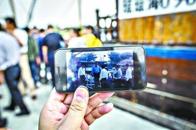昨日在潭门镇,渔民展示用手机拍到的国家主席习近平 本报特派记者 贾代腾飞 摄
