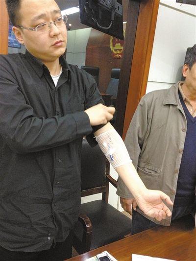 李先生(左)展示胳膊上的治療痕跡。昨日,李先生認為家具甲醛超標,導致自己患上白血病,將銷售方告上法庭。新京報記者 劉洋 攝