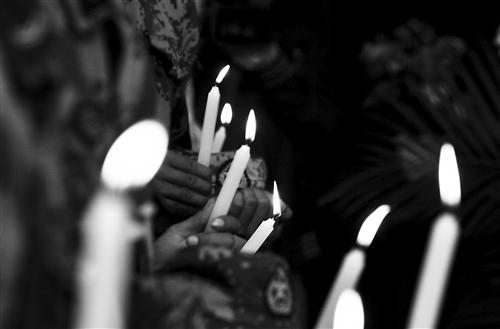战友们手捧蜡烛为烈士送行