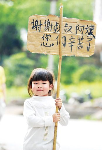 4月25日,雅安市天全县老场乡的公路边,小朋友向救援人员致谢。 本报记者王建军摄