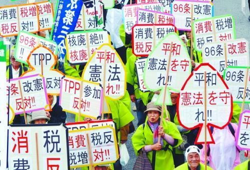 5月1日,大批民众在东京举行抗议集会。图为手举反对修改和平宪法标语牌的示威者。