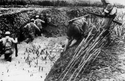 郊刘行战斗中,解放军战士越过竹签,涉过泥泞的壕沟,猛扑敌军地