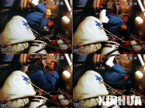10月14日16时,航天员费俊龙在飞船返回舱失重状态下连续作了数次前空翻,聂海胜用相机在旁边拍下了他翻跟头的镜头。     新华社记者查春明摄于北京航天飞行控制中心