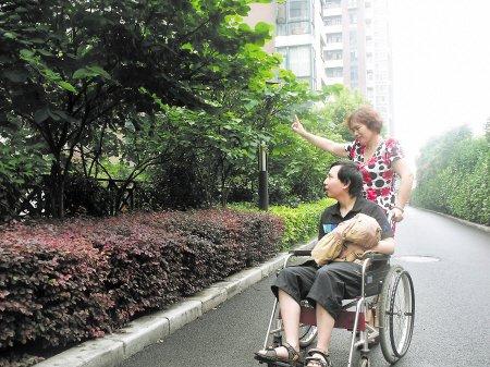 周长庚 简浩/几乎每天,周长庚都会推着轮椅,带着简浩在小区花园里散步,...