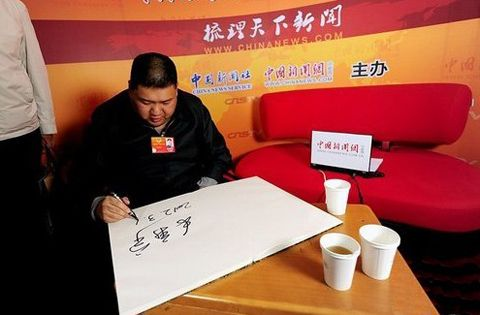 7、2012年3月10日,全国政协委员毛新宇在人民大会堂接受中新网记者采访,现场秀书法。