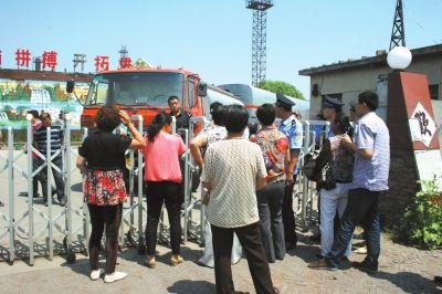▲7月11日,多人堵住位于沧州市南大港产业园区内的海通石油产品有限公司的大门,与大门内的大庆警方对峙。 京华时报记者张剑摄