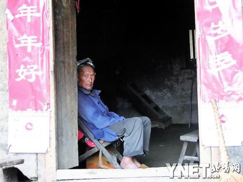 79的邻居闫修坤坐在门口。留守乡村的老人常用这种方式打发时光