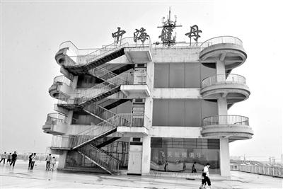 """据新华社电 近日,网友爆出山东滨州斥资1.2亿元建成的航母形建筑,原本被视为是""""城市标志"""",却因经营不善而变成""""水泥疙瘩""""。"""