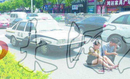 """事故发生后,警车司机(右)下车查看伤者并拨打120,俩""""领导""""稳坐车内引发围观者不满。"""