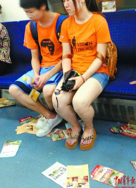 8月19日,北京地铁二号线上,一对年轻情侣望着脚下的售房传单。本报记者 杨杰摄