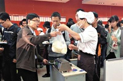 昨日,北大农园食堂,一中年男子购买了十余个馒头之后刷校园卡付钱,工作人员在刷卡处提示他食堂规定每种主食限购三个,请他下次注意。A16-A17版摄影/新京报记者 黄月