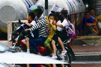 摩托车带四名小学生路上疾驶差点撞车