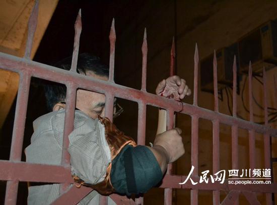 """男子""""挂""""在栅栏上(通讯员陈虹杉 摄)"""