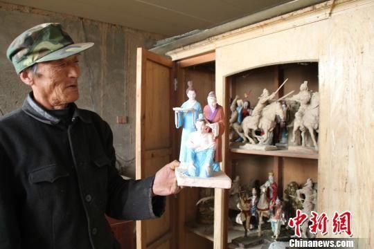 """图为张其林向记展示泥塑作品""""岳母刺字"""" 刘洋 摄"""
