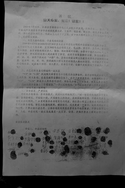 """4名案犯家属多年来一直四处上访,为子""""申冤"""",这份申诉书中征集了近800个村民的手印。"""