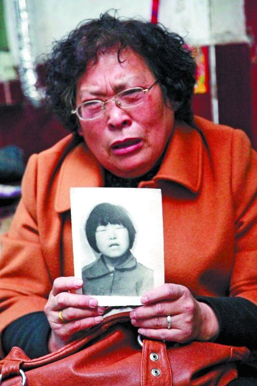 拿着女儿的照片,董翠英泪流满面。