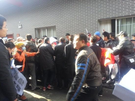 激动的人群开始向会场内涌入,被工作人员阻止,于是双方发生肢体冲突。