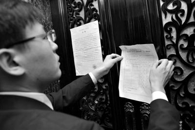 法官将公告等贴在涉案房屋门上。昨日,因该房主拖欠借款被法院强制执行。本组摄影/新京报记者 吴江