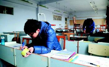 """上午9时许,三教一个教室门口贴出了""""已满""""的纸条。 本报记者 韩逸 摄"""