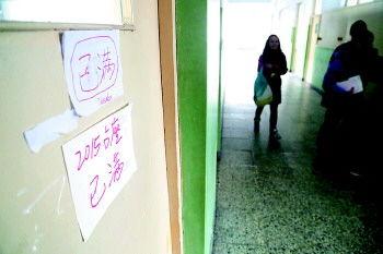 整个教室座位都被占了,有学生拿胶带将课本绑在桌子上。 本报记者 韩逸 摄