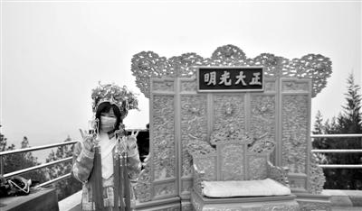 昨日,一名游客在北京景山公园内戴口罩着古装拍照。京城重污染5天无缓解。新华社发